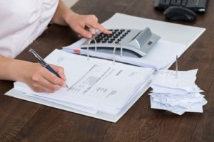 Close-up Of Accountant Calculating Receipt In Office